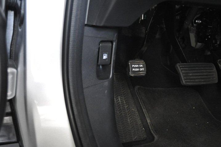 The secondary controls to release the fuel cap, apply the parking brake and release the hood are often found down below the dash on the left of the driver.