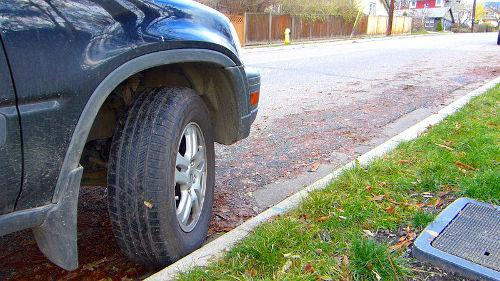"Parking uphill with a curb. When parking uphill with a curb, the steer tires are turned out toward the centre of the road. The vehicle is then allowed to roll backward, thus securing the vehicle against the curb. Think of Superman: ""Up, up & away!"""